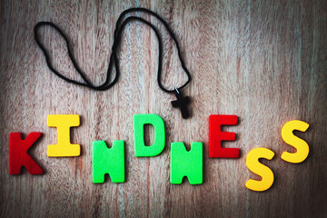 The word kindness written in  wooden background