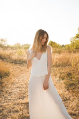 Beautiful blonde woman in a long white dress posing in the field. Boho style