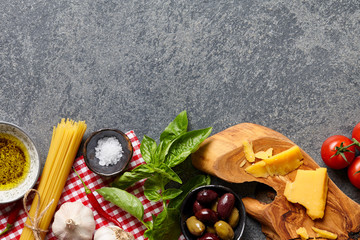 Italian food ingredients stone background with raw spaghetti, olives, basil leaves, parmesan cheese, garlic, olive oil and tomatoes.