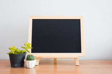 Cactus and blackboard on wood table