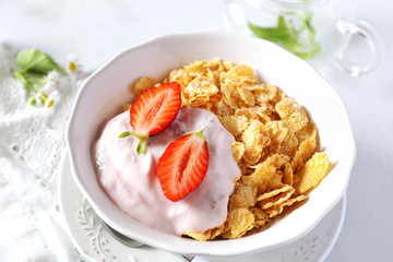 Corn flakes in bowl, yogurt, strawberries and chia seeds