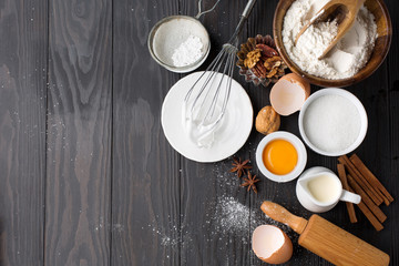 Baking ingredients for homemade pastry on dark rustic wooden background. Top view, flat lay style