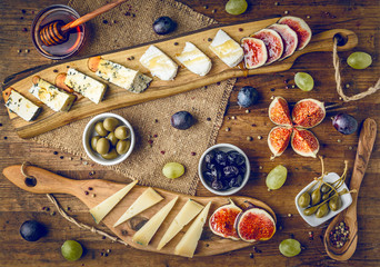 platter of italian cheeses with figs, olives, grapes and honey