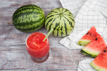 Watermelon juice, watermelons and slices on wooden background