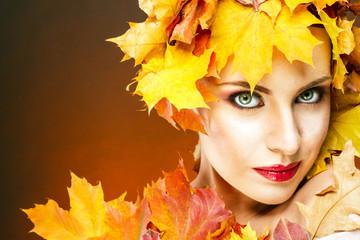 Красивая женщина с выразительными чертами лица в желтых кленовых листьях на коричневом фоне.