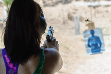 Woman in colorful top and ear muffs aiming handgun at practice range