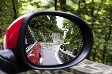 PKW-Außenspiegel mit Kurve einer Gebirgsstraße