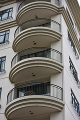 Corner of multi storey apartment building with rounded balconies.