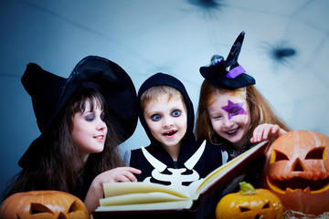 Three children in Halloween costumes reading a book among pumpkins and smiling