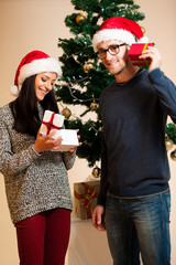 A young couple standing in front of the Christmas tree and givin