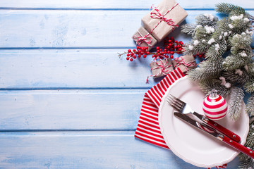 White plate, knife and fork, napkin and christmas decorations in