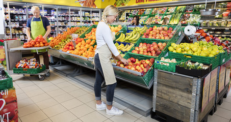 Workers Arranging Fruits In Supermarket