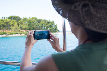 tourist taking a photo of an island with a smartphone from a boat
