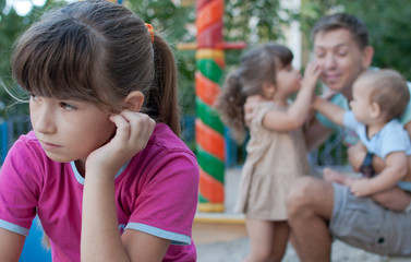 girl sad because of jealous younger sister to father