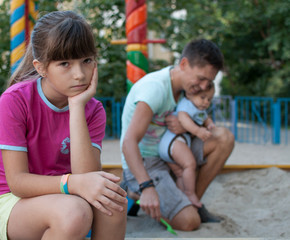 teenager girl jealous of her younger sister and brother