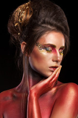 Creative make up with glitter, gold and red colors