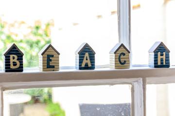 Little beach hut wooden ornaments on window frame composing the word BEACH