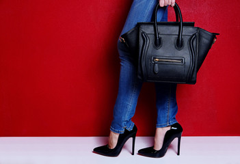 Wall Mural - woman posing in black high heel shoes and jeans with bag