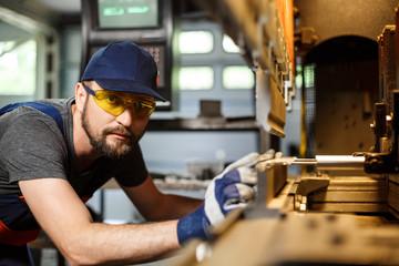 Portrait of worker near metalworking machine, steel factory background.