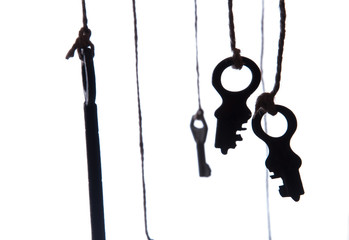 Many rustic keys hanging on string. Selective focus. Isolated