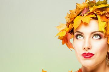 Красивая женщина с выразительными чертами лица в желтых кленовых листьях на оливковом фоне.