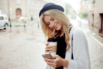 Cheerful woman in the street drinking morning coffee and use her smartphone.