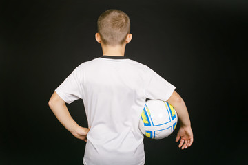 young football player with ball in hand. boy member of the football team. view from the back. empty space on white t-shirt for your text. isolated on black background.