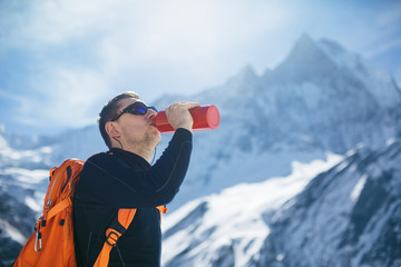 Hiker drinking water in mountains