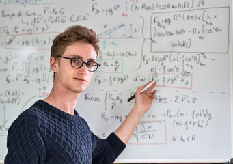Young student posing in front of a board with math calculation