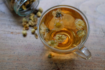 Chrysanthemum tea glass on wooden.