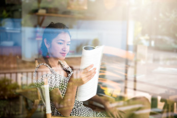 Young woman enjoying reading book sitting near window relaxing in her living with window reflection in the coffee shop