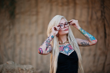 Young tattoo blonde girl on black dress and glasses posed backgr