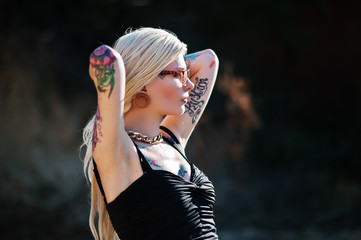 Young tattoo blonde girl with tunnel ear piercing on black dress