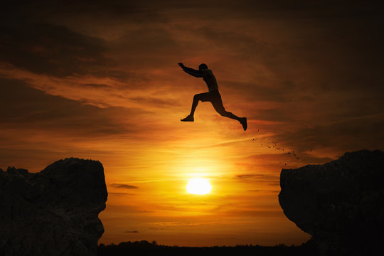 Silhouette of a man jumping over abyss at sunset with copy space