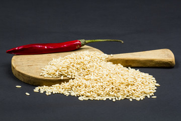 Composition with red pepper, paddy rice and wooden kitchen cutting board on dark background
