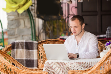 Man working on laptop at the wooden table outdoors