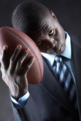 Businessman holding an American football isolated on black background