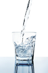 fresh water filling a glass isolated on white
