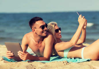 happy couple with modern gadgets lying on beach