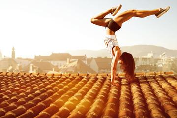 Frau macht einen Handstand auf Hausdach