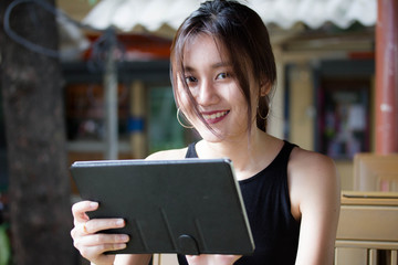 Portrait of thai adult glasses student university beautiful girl using her tablet.