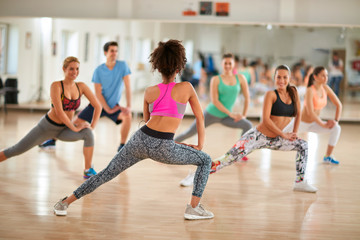 Female instructor show exercises to fitness group
