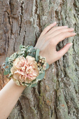 Dusty pink carnation wrist corsage on a hand