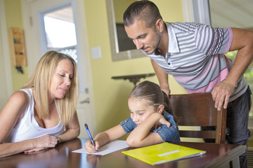 parents helping son with homework in home interior