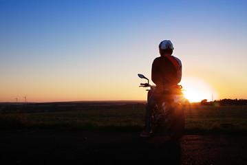 Junger Motorradfahrer im Sonnenuntergang / Young biker while sunset Wall mural