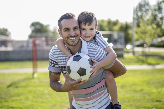 man with child playing football on field