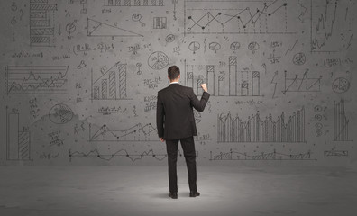 Salesman with business charts on wall