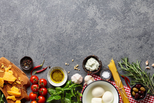 Italian food ingredients background with raw spaghetti, different kinds of cheese, olives, basil leaves, rosemary, garlic, chili pepper, olive oil and tomatoes.