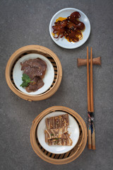 Assorted Asian appetizers; sliced pig ears, beef shank and baby octopus in mini bamboo baskets
