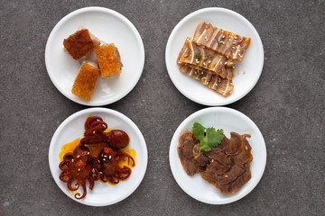 Assorted Asian appetizers on white plates:  octopus in spicy sauce, sliced beef shank, pigs ears, crispy barbecue pork . Dark gray background